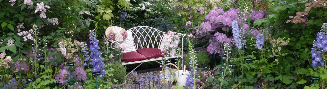 Weiße Bank in romantischem Garten