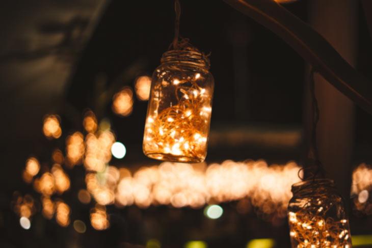 Hängendes Glas mit leuchtender Lichterkette im Garten