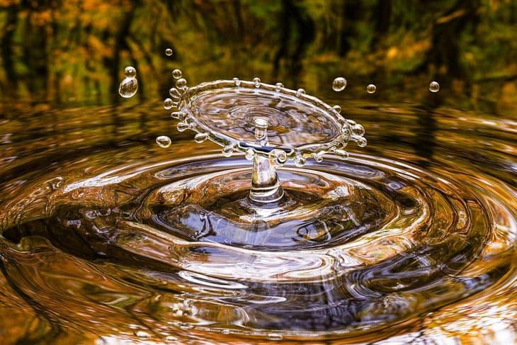 Wassertropfen fällt in Pfütze